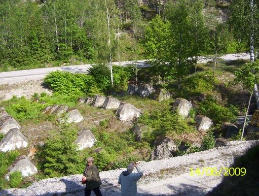 Draktänder i fyra rader mot vägen. Över vägen fanns en vägspärr. Inga rester finns efter den längre.
